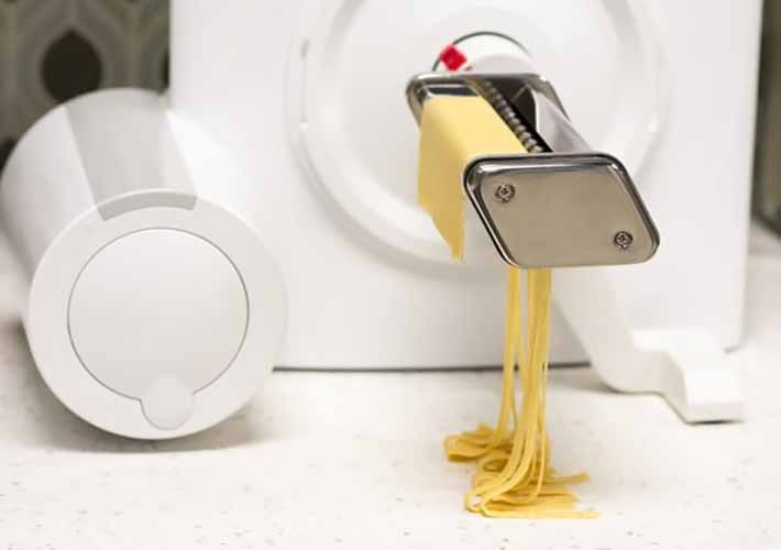 Horizontal image of a pasta maker attachment on the side of a mixer base with a sheet of yellow pasta being run through it.