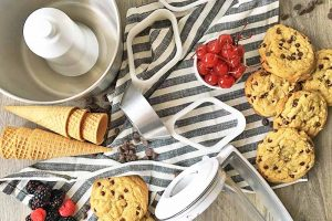 Horizontal image of assorted kitchen tools, cones, and cookies on a striped towel.