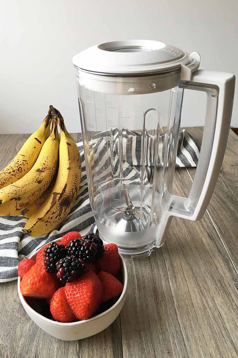 Vertical image of a blender with bananas, fruits, and a striped towel.
