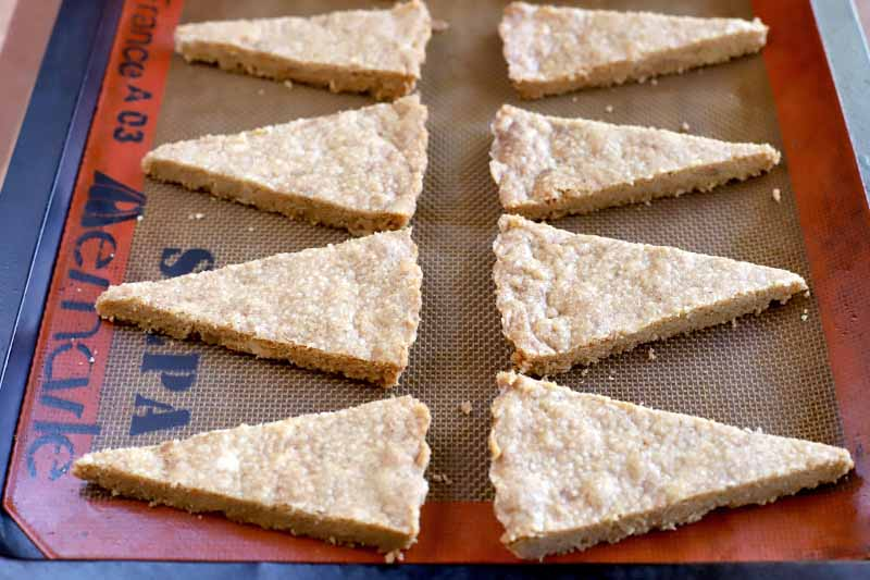 Eight triangle-shaped pieces of shortbread arranged in rows on a Silpat silicone pan liner.