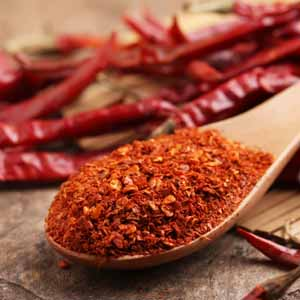 A close up of ground cayenne pepper in a wooden spoon with dried red chilies in the background.