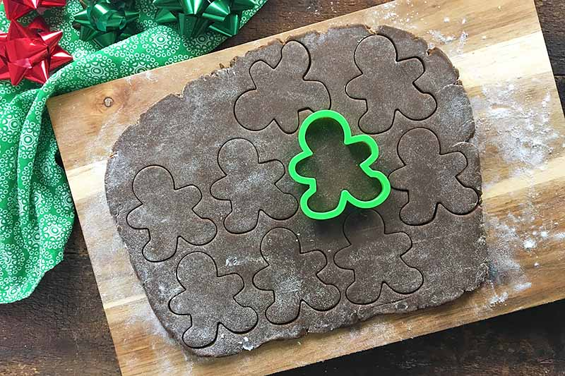 Horizontal image of rolled out dark brown dough with cut-outs and a green cookie cutter.