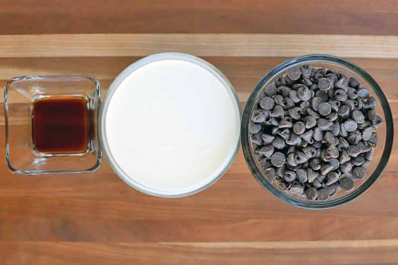 Overhead shot of one square and two glass bowls of vanilla extract, cream, and dark chocolate chips, on a striped wood surface.