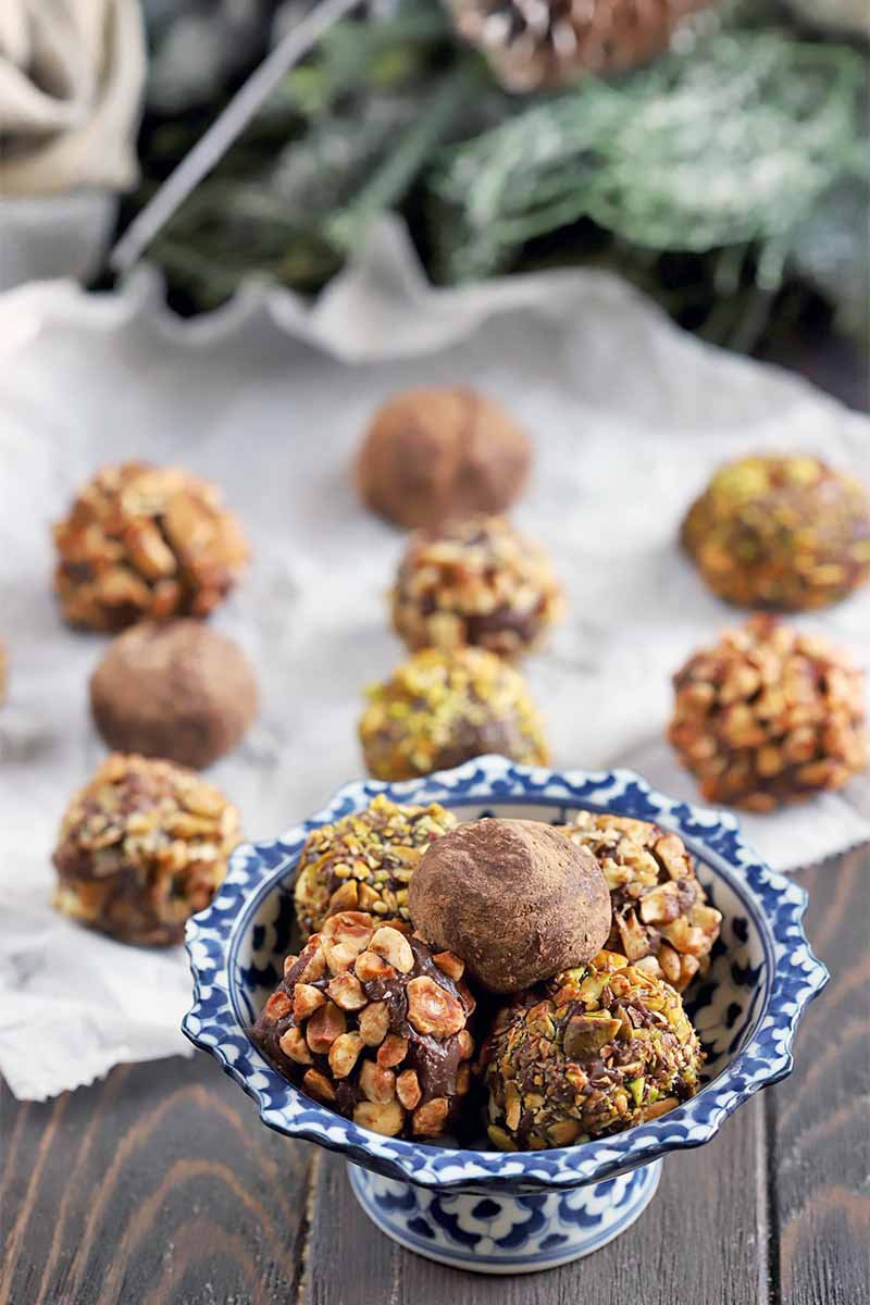 Homemade chocolate truffles coated in chopped nuts and cocoa powder are in a small blue and white ceramic dish in the foreground, with more arranged on a piece of white parchment paper in soft focus in the background, with artificial greenery coated with artificial snow, on a dark brown wood surface.