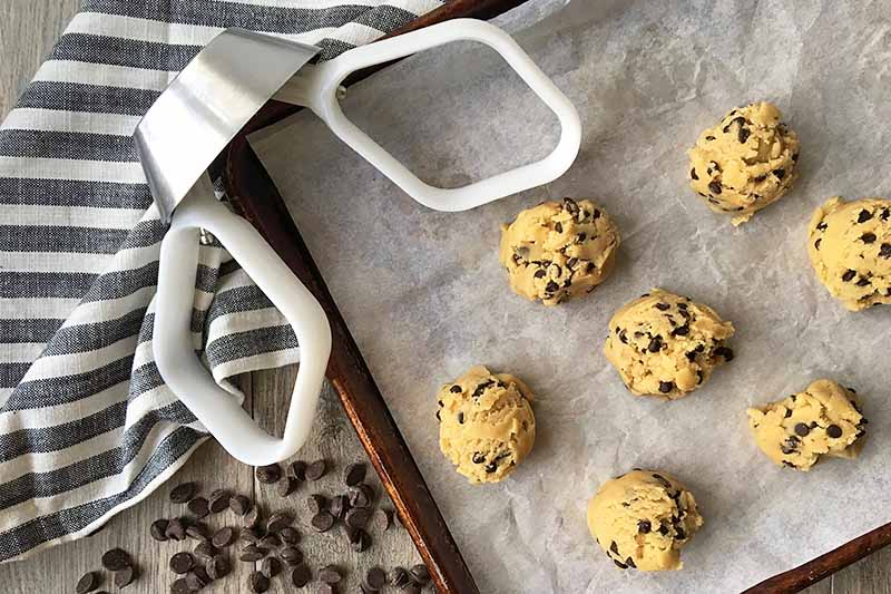 Horizontal image of two white paddles attache to a metal drive on a sheet pan with cookie dough rounds.