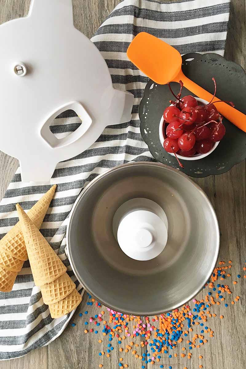 Vertical image of an ice cream maker, cover, cherries, orange spatula and ice cream cones on a striped towel.