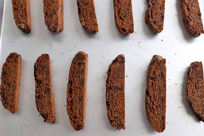 Top-down shot of sliced biscotti arranged in two rows on a baking sheet.