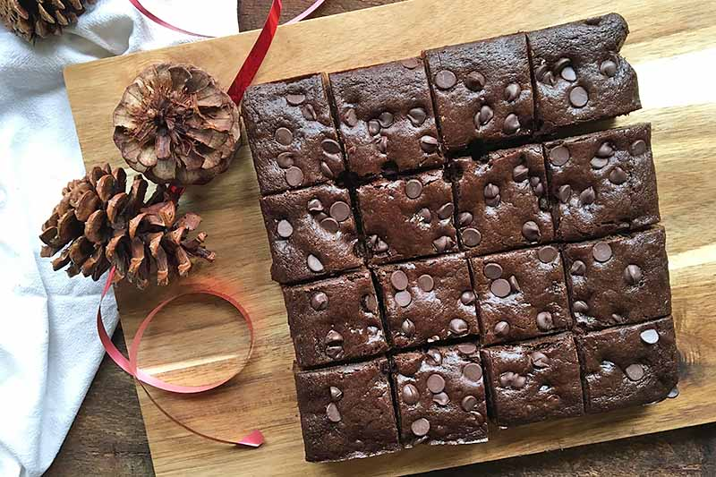 Horizontal image of chocolate gingerbread cut into squares on a wooden cutting board next to pinecones and a red ribbon.