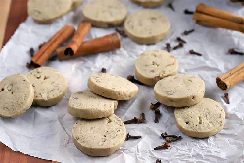 Oblique shot of small round cookies with whole cloves and cinnamon sticks on a piece of crumpled parchment paper on a brown wood surface.