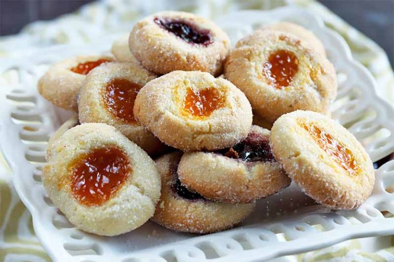 Jam-filled thumbprint cookies on a square white serving dish.