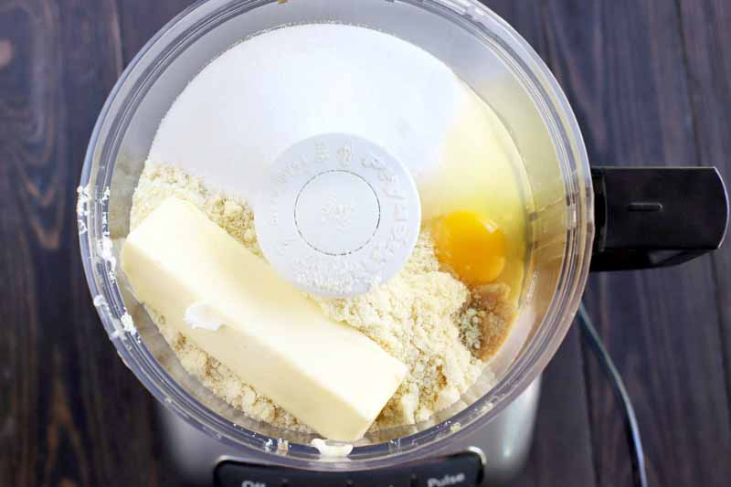A stick of butter, sugar, almond meal, and an egg in a plastic food processor canister, on a dark brown wood table.