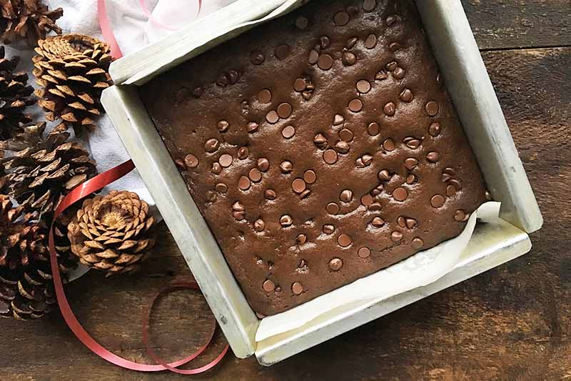 Horizontal image of a metal square pan with a baked cake next to pine cones, a red ribbon, and a white towel.