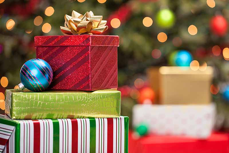 A stack of presents wrapped in holiday paper with a gold bow on top and a blue glass tree ornament, with more wrapped gifts and a decorated evergreen tree in soft focus in the background.