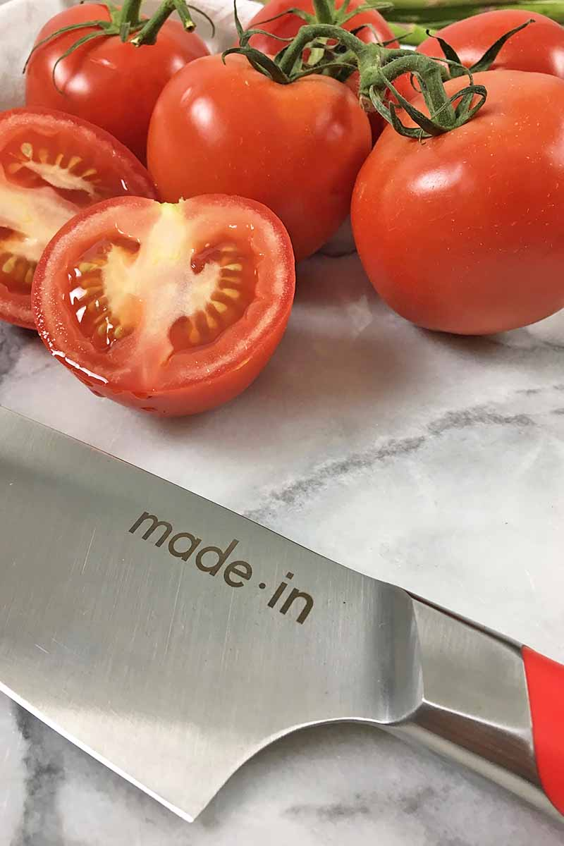 Vertical close-up image of a knife with sliced and whole tomatoes.