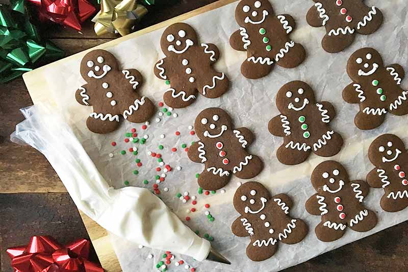 Horizontal image of decorated Christmas cookies on a work surface lined with parchment paper.