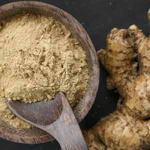 Top down view of a wooden bowl full of ginger powder with a couple of fresh ginger roots sitting next to it.