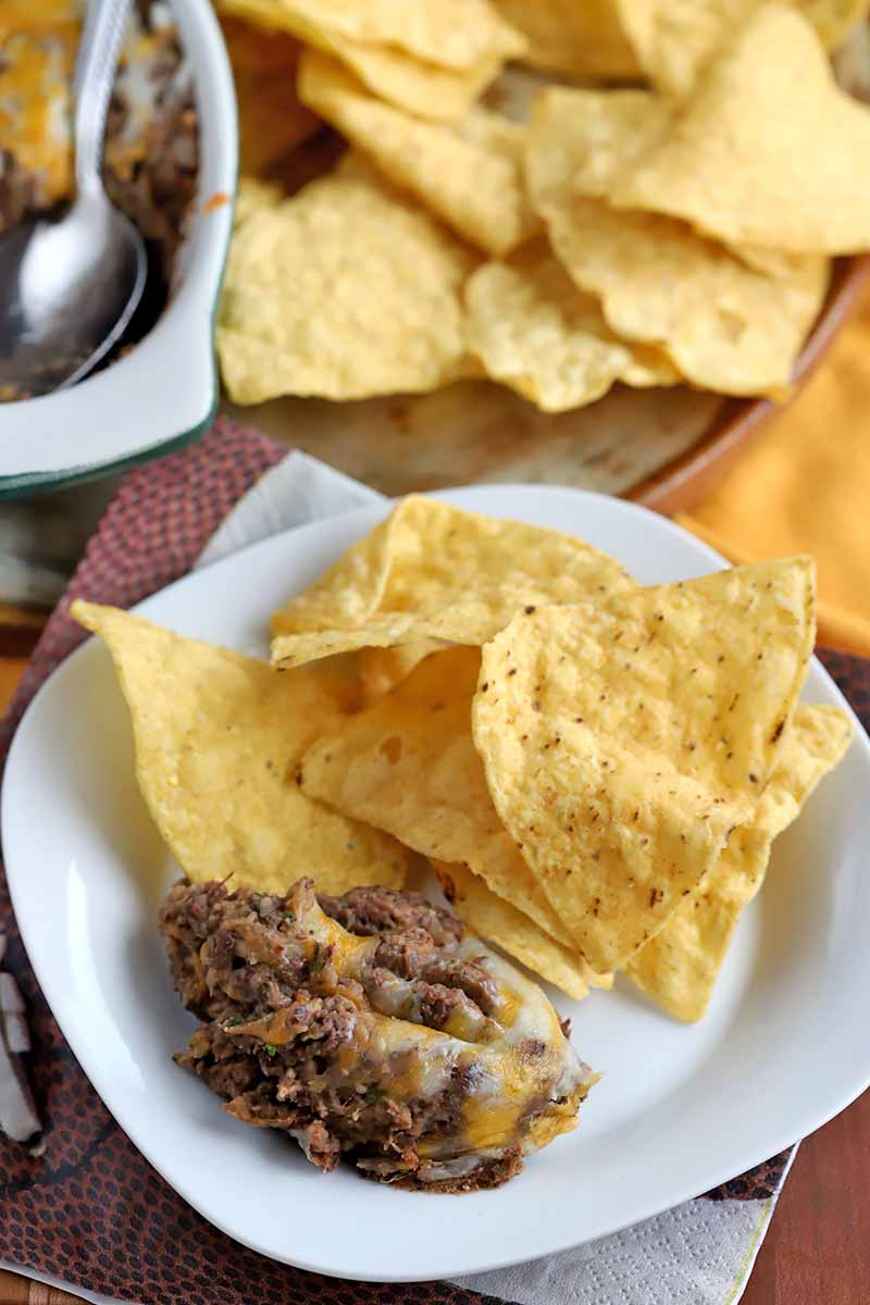 Vertical oblique shot of a plate of yellow tortilla chips and a serving of bean dip, with more in a ceramic serving dish with a spoon beside a pile of chips in the background.