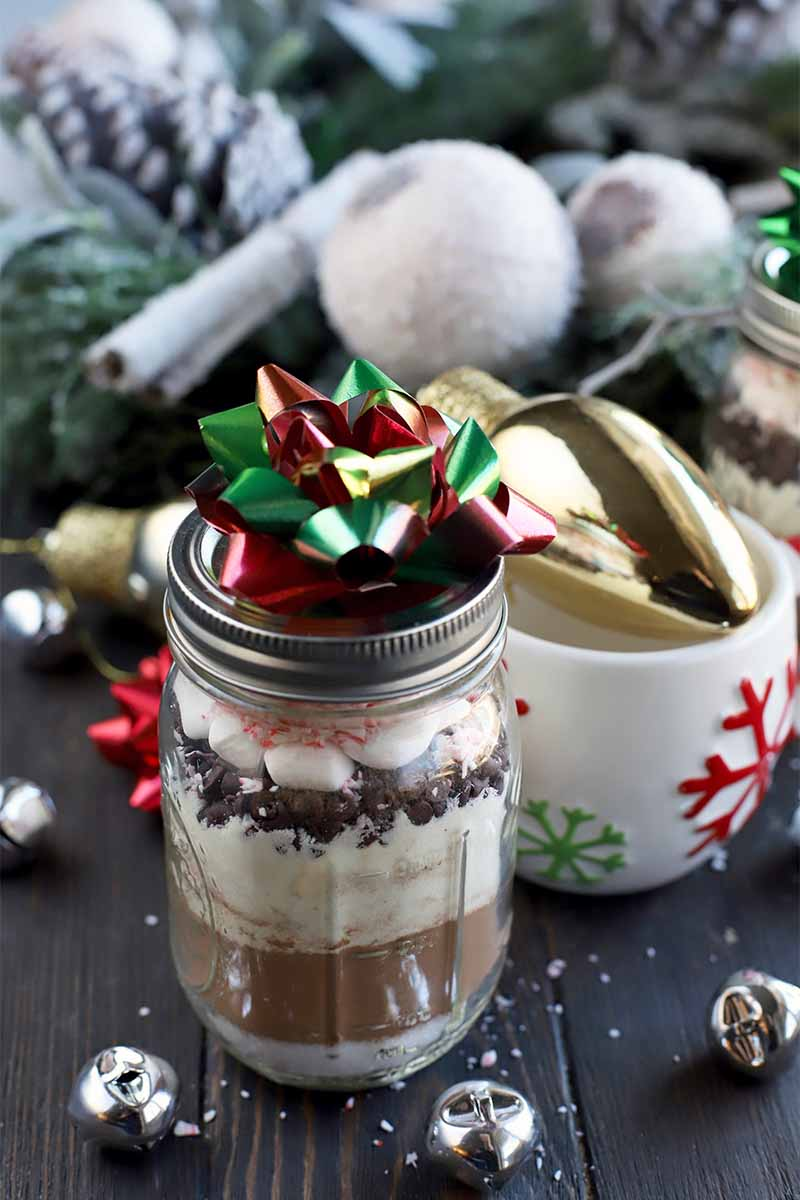 A glass jar filled with layered homemade hot chocolate mix and topped with a bow is in the foreground, with a holiday mug and decorative Christmas baubles in the background and scattered to either side on a dark brown wood table.