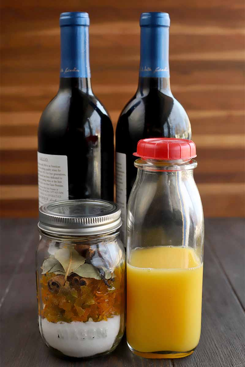 Vertical image of two bottles of red wine, a jar of sugar, candied citrus peel, and mulling spices, and a glass bottle of orange juice with a red plastic lid, on a dark brown wood table with a brown striped wood background.