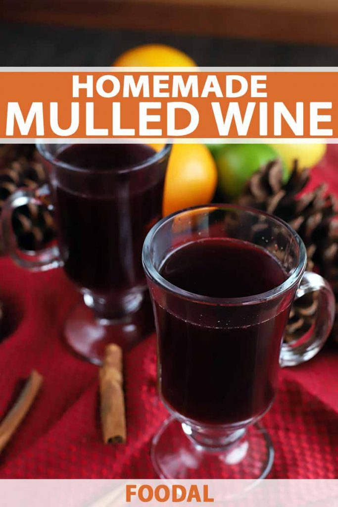 Vertical image of two glass mugs of mulled wine with cinnamon sticks, pine cones, oranges, lemons, and limes on a gathered red cloth on top of a brown wood table, printed with orange and white text.