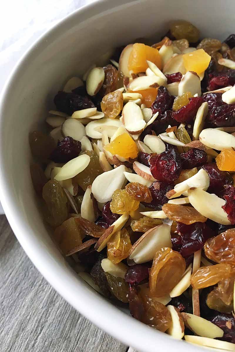 Vertical close-up image of a bowl of assorted fruits and nuts.