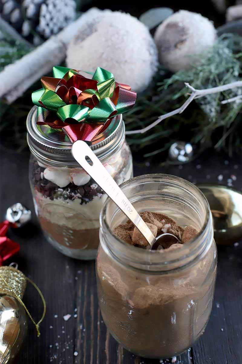 One glass jar of layered hot chocolate mix is topped with a red and green bow, and another in the foreground contained a mixture stirred together with a metal measuring spoon, with holiday decorations and bows on a dark brown wood surface.