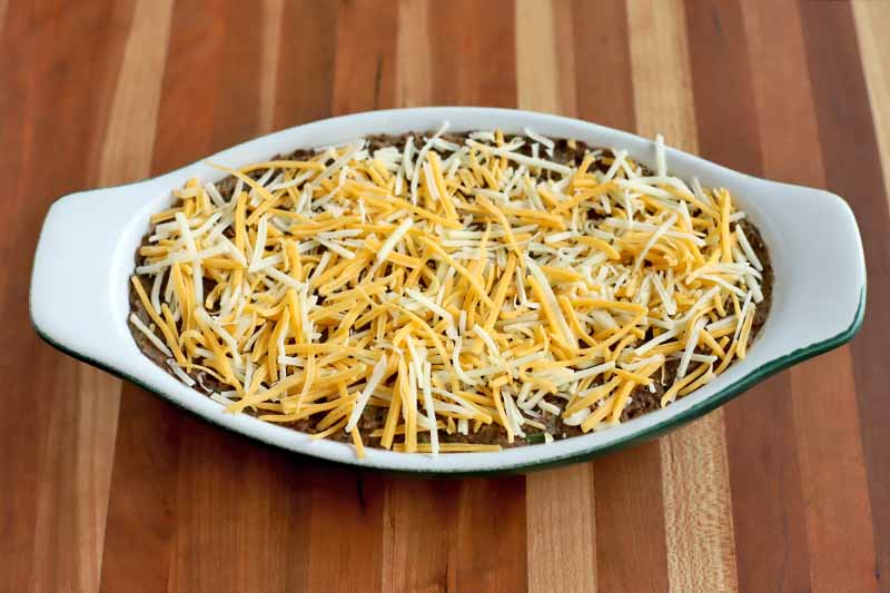 Overhead shot of bean dip in an ovoid ceramic baking dish with built-in handles, topped with shredded cheese, on a striped wood surface.
