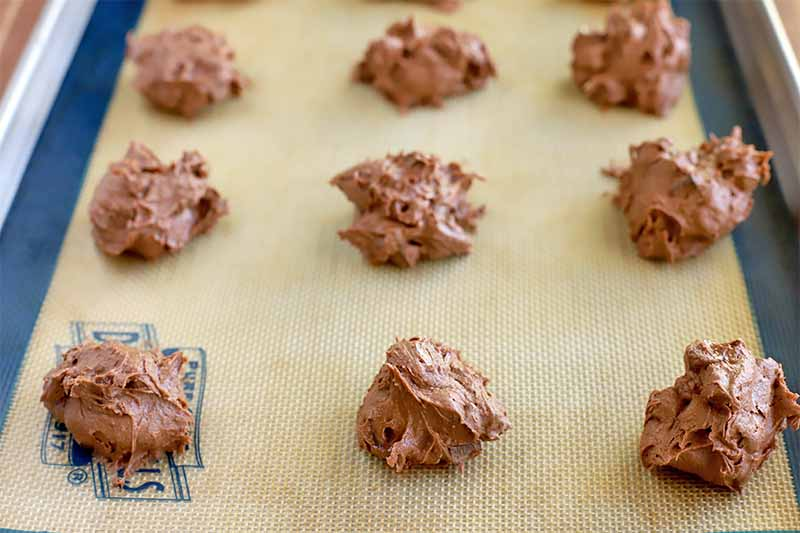 Nine dollops of chocolate cookie dough are arranged in rows on a beige and blue silicone pan liner in a metal baking sheet pan.