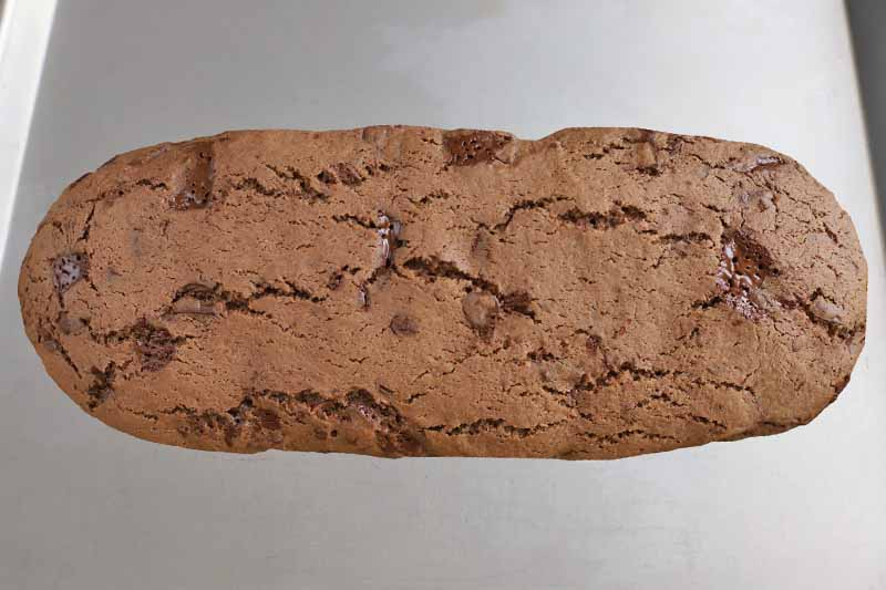 A baked log of chocolate biscotti dough on a baking sheet.