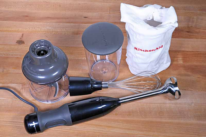 The KitchenAid KHB2351 3-Speed Hand Blender set with all of the attachments including a wire whisk, food processor, and blending cup on a maple butcher block surface.