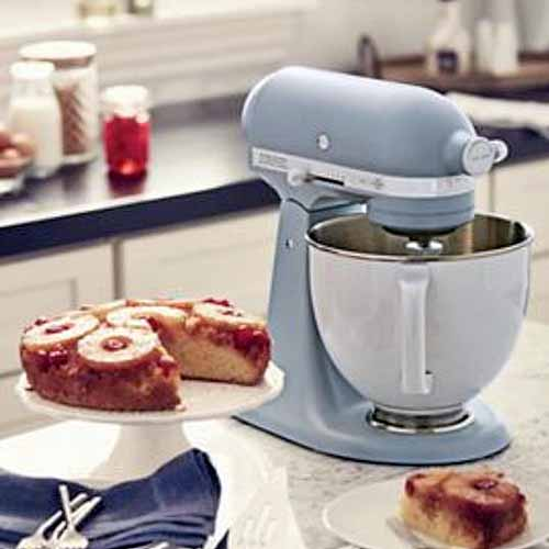 A pale blue limited edition KitchenAid stand mixer on a kitchen counter with a cake server and plate of pineapple upside down cake, and another countertop in the background across the room.