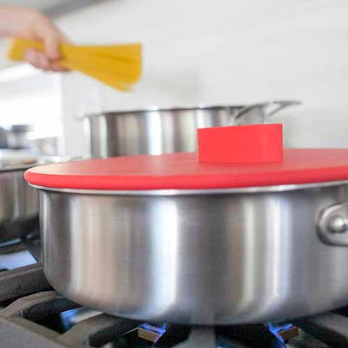 Closely cropped image of a red silicone lid on top of a pan on a gas stove, with a hand in the background holding a fistful of uncooked spaghetti, about to drop it into a tall stockpot on the left rear burner, with a white background.