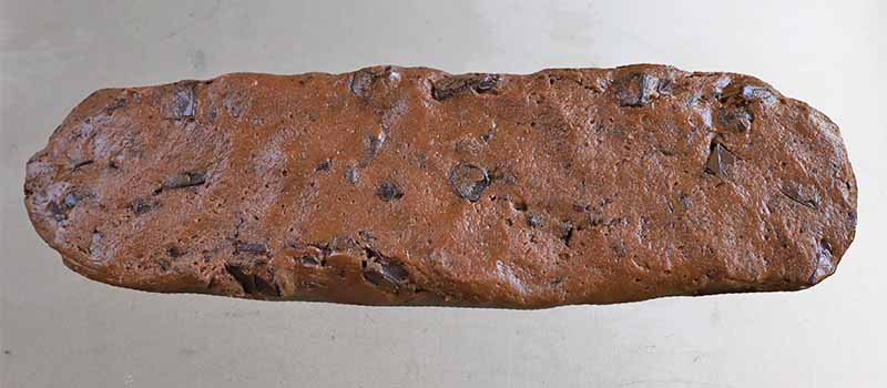 Chocolate dough formed into a log, on a baking sheet.