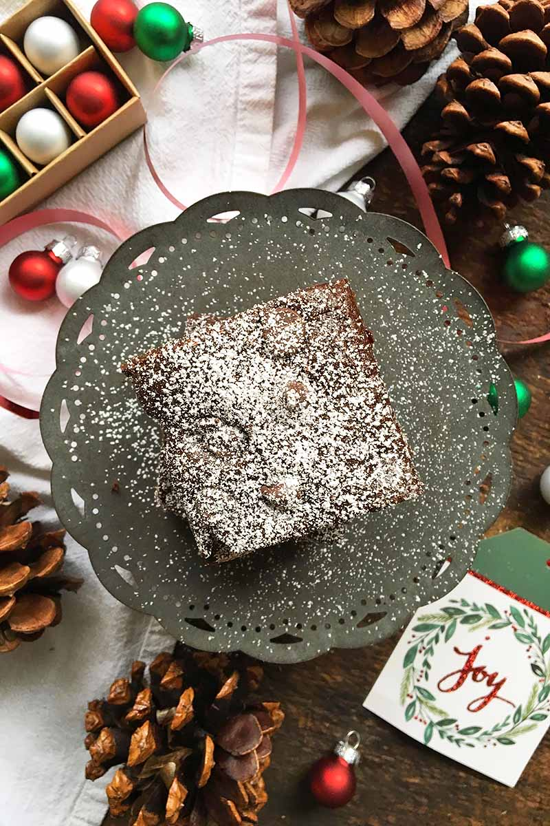 Vertical image of a dessert square dusted in powdered sugar on a stand over a white napkin, assorted Christmas decorations, and pinecones.