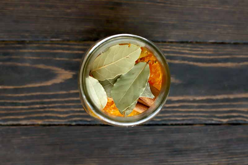 Overhead shot of a jar filled with candied citrus peel and dried bay leaves, on a dark brown wood table.