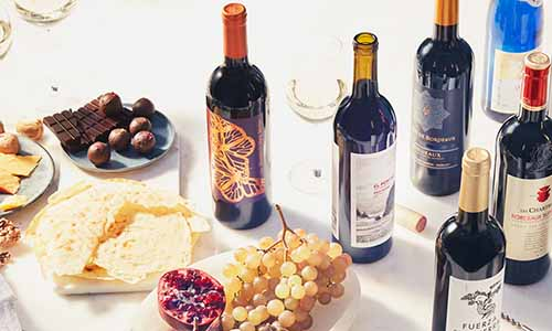 Closely cropped image of various bottles of red wine with wine glasses, appetizers, grapes, and a pomegranate, on a white background.