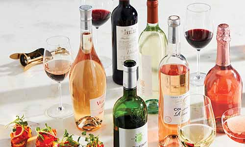 Closely cropped oblique image of various bottles of red, white, and rose wine, with filled wine glasses.