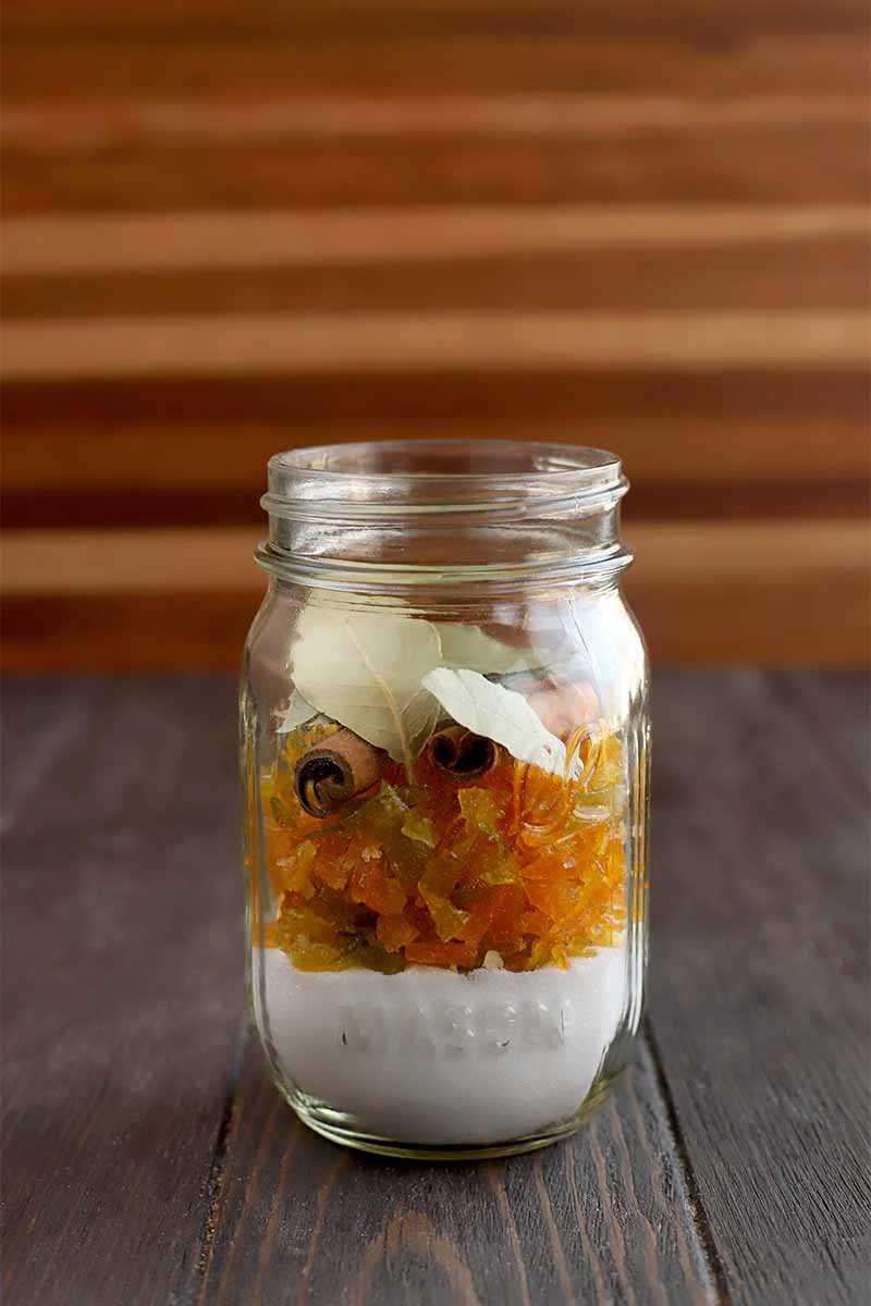 Vertical image of a mason jar filled with layered sugar, candied citrus peel, and whole spices, on a dark brown wood table against a striped brown background.