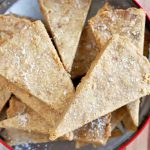 Overhead shot of a red and silver metal cookie tin filled with triangular pieces of brown butter shortbread, on a wood surfaced topped with a cloth.