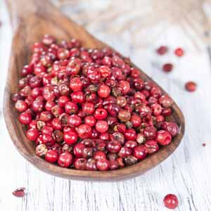A wooden spoon full of pink peppercorns.