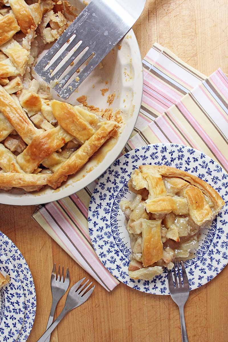 Top down view of a single slice of apple pear pie in the lower right corner sitting on a blue and white patterned porcelain saucer. The remainder of the pie sits to the upper left in a baking dish. A couple of folks, a place mat, and a pie serving utensil is also in the photo.