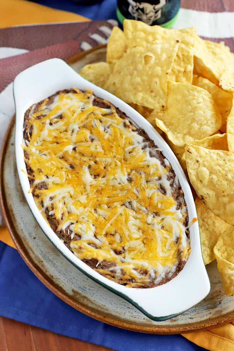 Vertical oblique shot of an oblong ceramic baking dish filled with black bean dip, on a plate beside a pile of yellow corn tortilla chips, with blue, white, and football-themed napkins.