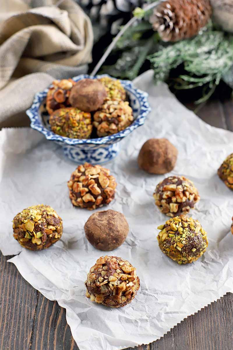 Hazelnut, pistachio, and cocoa powder-coated homemade chocolate truffles arranged on a crumpled piece of white parchment paper and in a small blue and white ceramic dish, with a gathered beige cloth, artificial greenery, and pine cones in the background on a dark brown wood surface.