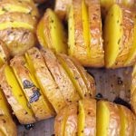 Close up of a sage hasselback potatoes in a baking pan.