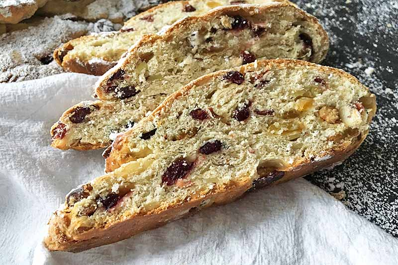 Horizontal image of three slices of fruit and nut bread.