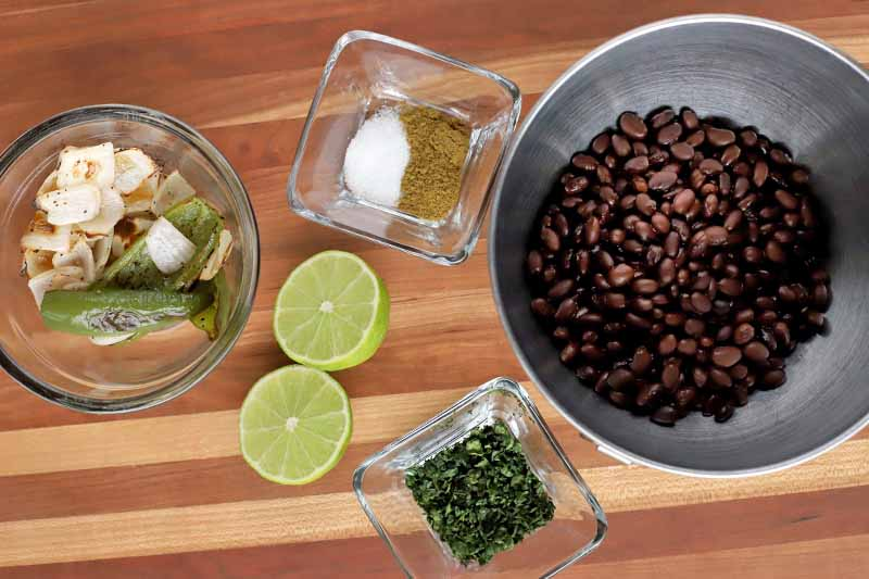 Overhead shot of square and round glass bowls of roasted onions and peppers, seasonings, and chopped fresh herbs, with a halved lime and a stainless steel bowl of black beans, on a brown striped wood surface.