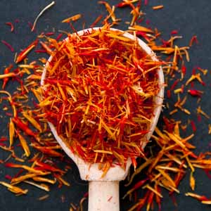 A wooden spoon full of fresh red and yellow saffron threads.