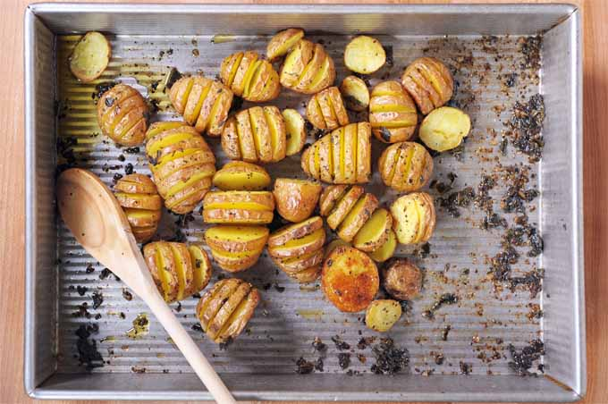 Top-down view of a roasting pan full of sage hasselback potatoes. A wooden spoon also sits inside the pan.