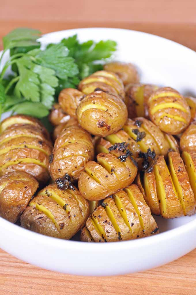 A white porcelain bowl full of hasselback potatoes flavored with butter and sage.