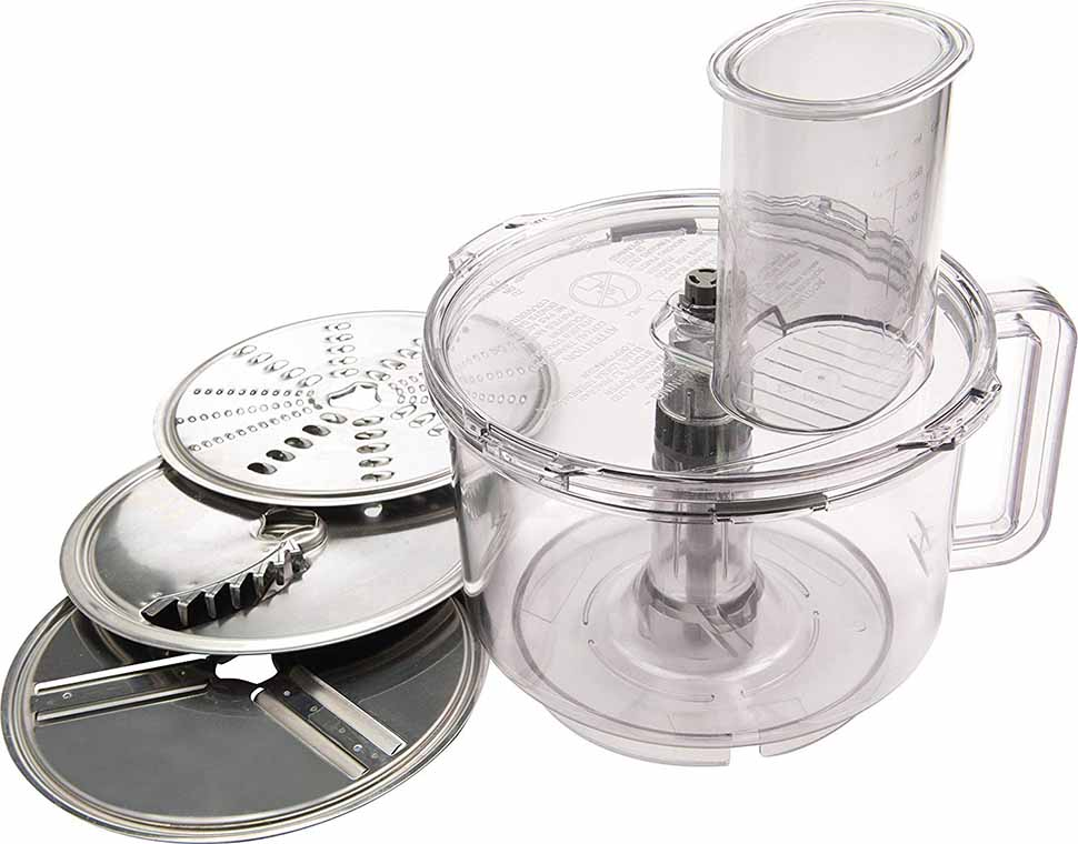 Horizontal image of a small clear food processor with three metal plate shredding options.